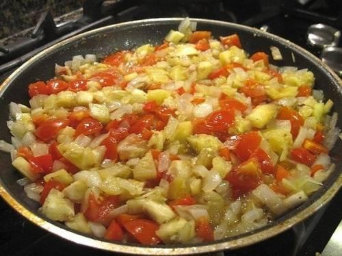 К баклажанам кидаем все порезанные овощи, подсаливаем их и тушим в воде минут 4-5. Не забываем, помидоры бросаем в последнюю очередь, предварительно сняв с них кожицу.