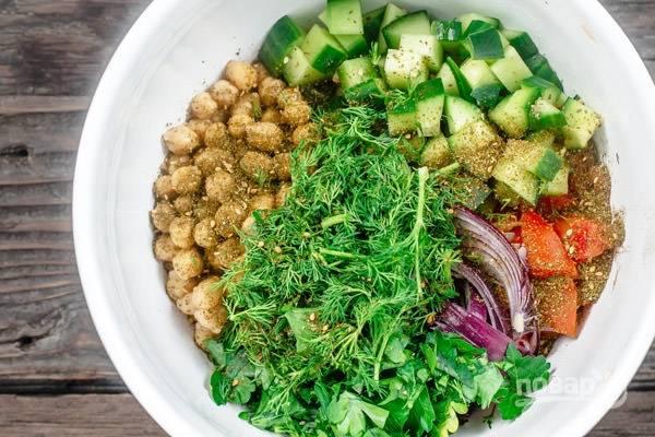 Заранее отварите нут и остудите. Соедините его в салатнице с нарезанными помидорами, луком и огурцами. Добавьте измельчённую зелень и приправу.