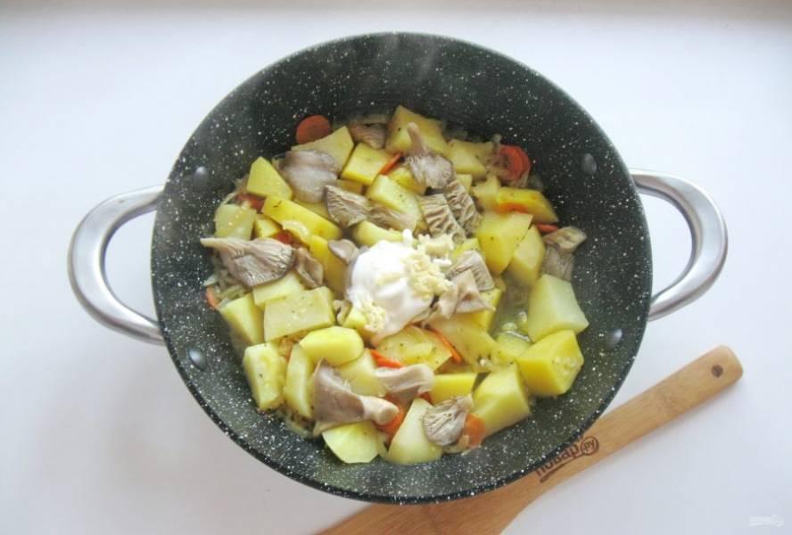 Тушите картофель с овощами и грибами до готовности. В конце добавьте сметану и чеснок.