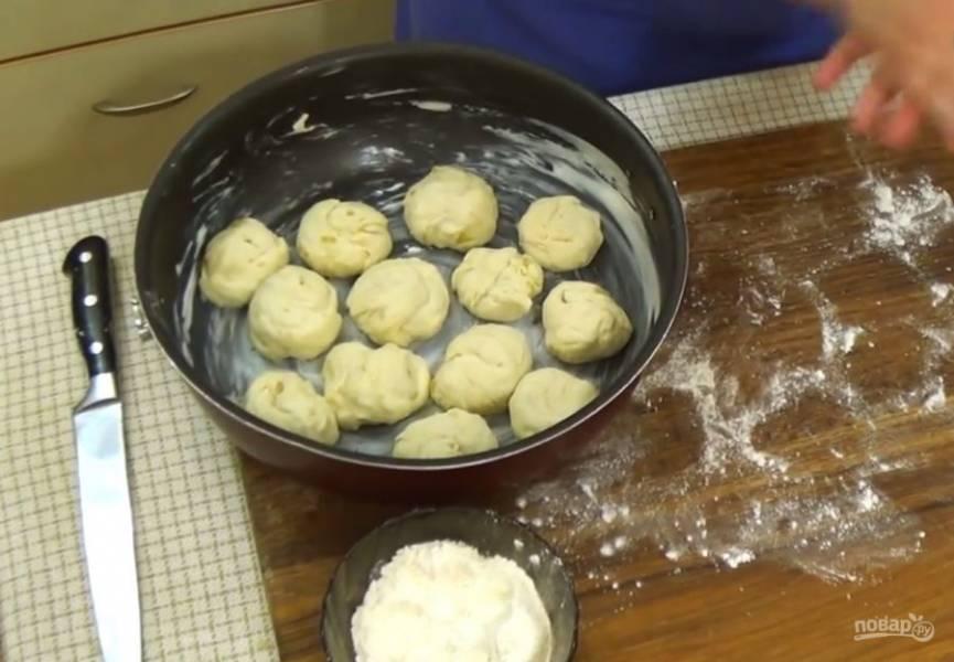 4. Сформируйте из каждого кусочка теста шарик, это будет булочка. Форму смажьте сливочным маслом и выложите в нее булочки на расстоянии друг от друга. Форму с булочками накройте полотенцем и оставьте в тепле на 30-40 минут.