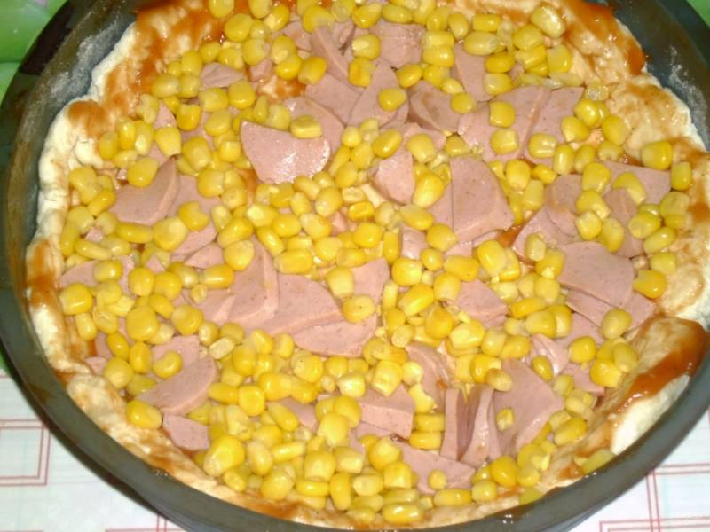 3.На подготовленное тесто выкладываю кетчуп, размазываю его по всей поверхности, добавляю кукурузу и колбасу.