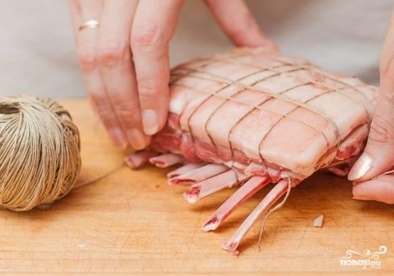 3. Зачистите края ребер от пленки и мяса. Возьмите кулинарный шпагат и несколько раз оберните кусок мяса. Это поможет мясу сохранить форму.