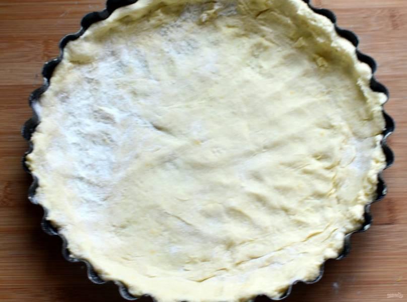 Распределите тесто руками по форме, прижимая донышко и формируя края. Чуть наколите дно, накройте его бумагой для выпечки и насыпьте сверху сухой фасоли. Выпекайте основу в разогретой до 200 градусов духовке минут 7-8. Края начнут чуть румяниться. Высыпьте фасоль и снимите бумагу, выпекайте еще 3-4 минуты.