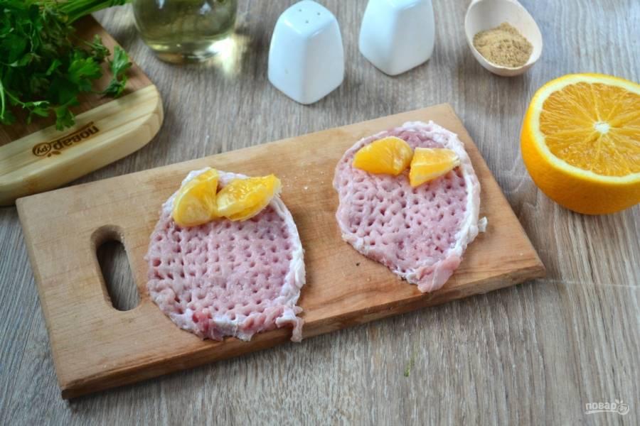 Порежьте свиную вырезку как на отбивные. Каждый ломоть отбейте с одной стороны, с обеих сторон посолите и поперчите по вкусу. На каждый ломтик положите по дольке апельсина.