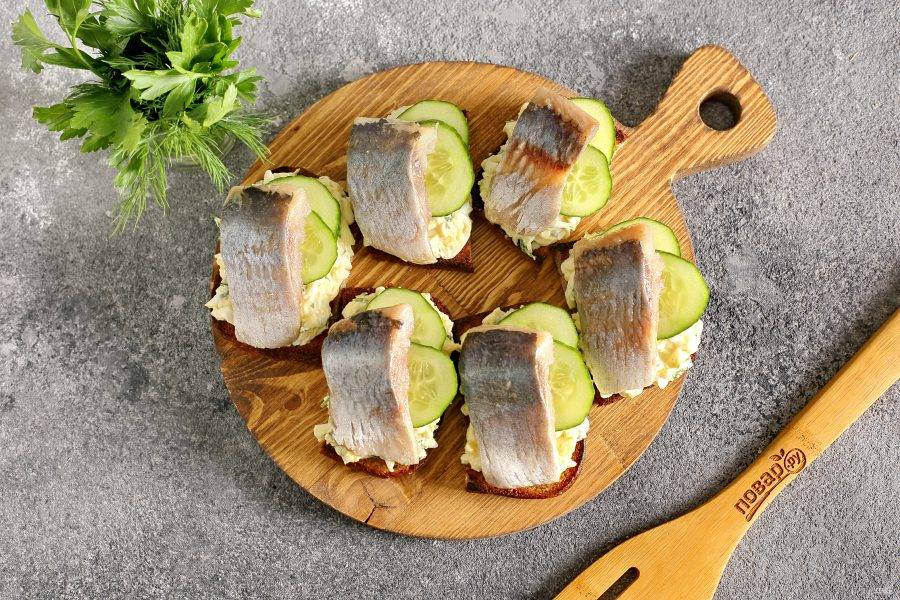Украсьте бутерброды свежим огурцом нарезанным кружочками. Бутерброды с селедкой готовы.