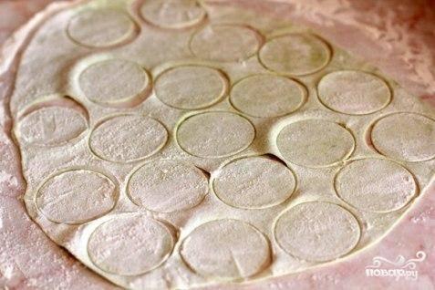 Раскатываем тесто в тонкий блин, при помощи формочки или обычного стакана разрезаем на кружочки.