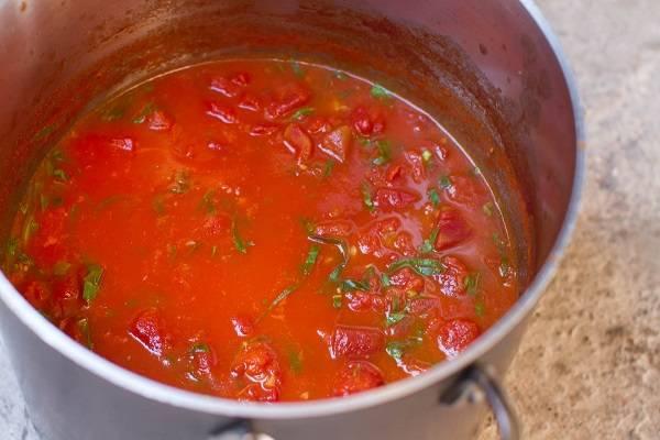 3. Теперь можно заняться соусом. В сотейнике разогрейте пару ложек оливкового масла. Очистите чеснок, измельчите и немного обжарьте его. Отличным ингредиентом, который прекрасно дополнит этот простой рецепт баклажанов в томатном соусе, станет лук. Вымойте и обсушите помидоры, измельчите и добавьте их в сотейник. Обжарьте на среднем огне пару минут. Добавьте по вкусу соль, сахар, можно перец. Затем снимите с огня, и добавьте измельченный базилик.