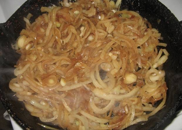 Немного обжариваем лук на сковороде, на которой готовились рёбрышки. Лук будет обжариваться в жире, который выделился от рёбрышек.
