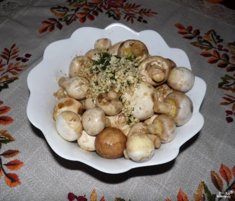 Шампиньоны хорошо промойте и очистите. Нарезать их не нужно, они будет запекаться целиком. Поэтому выбирайте не слишком большие грибы. Положите грибы в тарелку и присыпьте их укропом с чесноком.