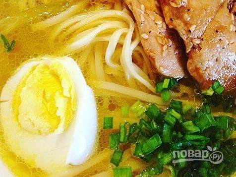 Выложите в каждое блюдо немного обжаренной в кунжуте курицы, добавьте по половинке отварного куриного яйца и присыпьте все нашинкованным зеленым луком. Подавайте суп горячим.