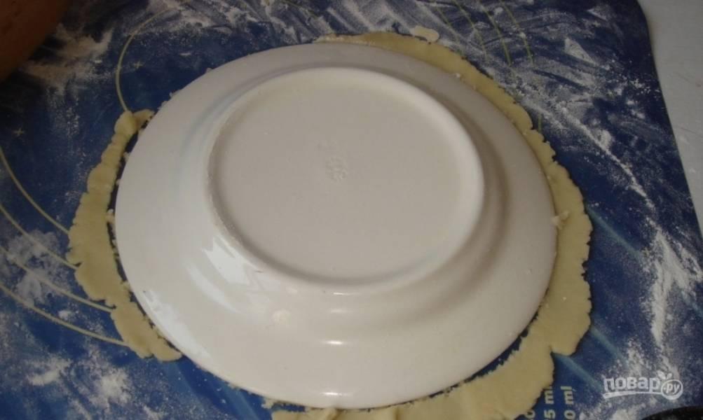 Все куски теста раскатайте при помощи скалки или бутылки максимально тонко, как только сможете. Затем при помощи специальной формочки или же обычной тарелки вырежьте ровные круги. Остатки теста не выбрасывайте, они еще пригодятся.