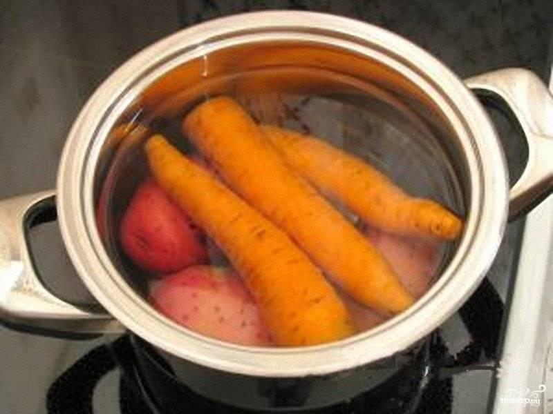 1. Первым делом вымойте морковь и картофель, выложите в кастрюлю и залейте водой. Поставьте на огонь и после закипания варите до мягкости. После залейте холодной водой и остудите.