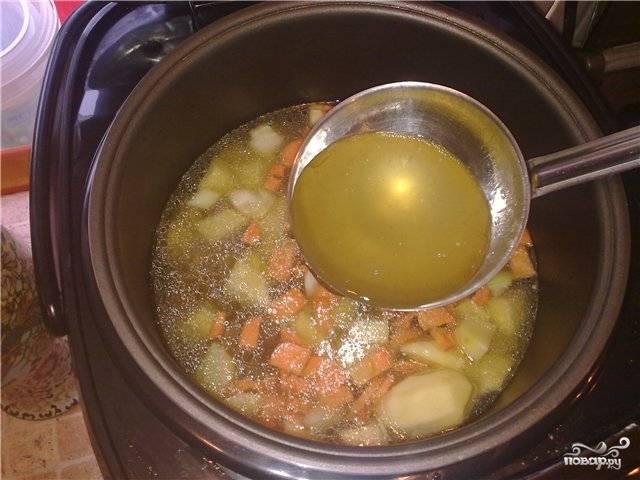 К мясу кладем картошку и морковь, заливаем бульоном, который надо процедить, включаем режим тушение на 40 минут.