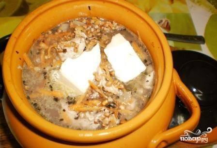 По истечении времени аккуратно извлекаем горшочек из духовки и выкладываем в него предварительно промытую гречку. Доливаем еще пол стакана кипятка (так чтобы жидкость была на 1-1,5 сантиметра ниже края), солим, аккуратно перемешиваем и сверху добавляем кусочек масла. Теперь его можно возвращать в духовку, закрыв крышкой. Готовим еще пол часа, а когда время выйдет, выключаем огонь и  20 минут даем постоять горшочку в духовке.