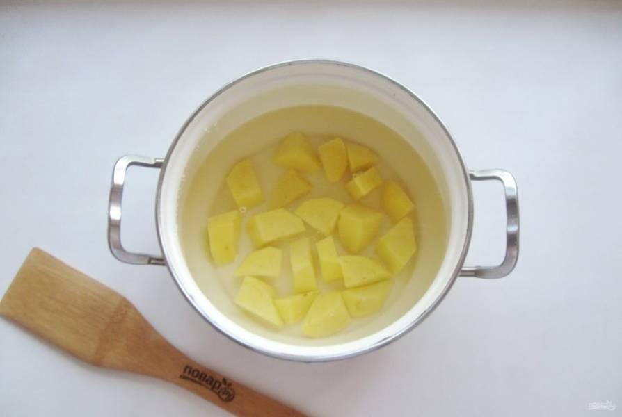 В кастрюлю налейте воду, выложите нарезанный кубиками картофель.