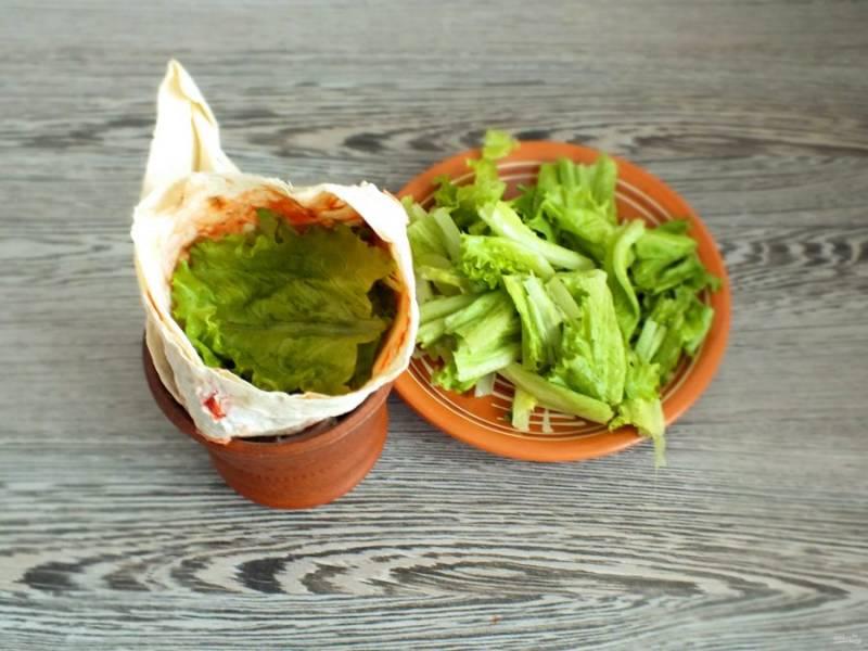 Для удобства наполнения лаваша, перенесите его в бокал. Салатный лист порвите руками на мелкие кусочки. Наполните лаваш салатным листом. Количество определяйте по вкусу.