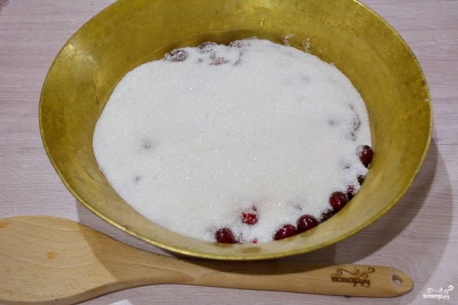 К ягодам добавьте сахар, перемешайте. Косточки из ягод мы не удаляли. Они при варке дают вкус и улучшают вкус джема. На среднем огне ставим вариться джем.