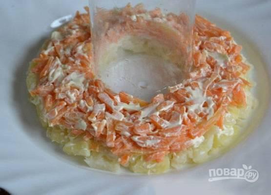 И приступаем к сборке салата. В центр плоской тарелки ставим стакан или небольшую баночку, а вокруг нее выкладываем слоями сначала картофель, посолим и поперчим, смажем майонезом. Затем морковь смешаем с чесноком и выложим на картофельный слой.