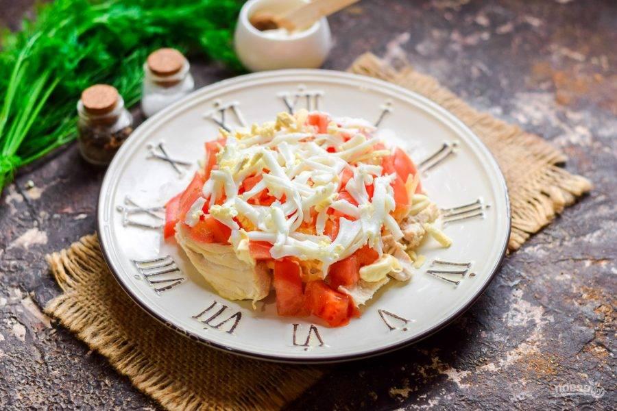 Куриное яйцо отварите вкрутую, почистите и натрите на средней терке. Посыпьте яйцом слой томатов.