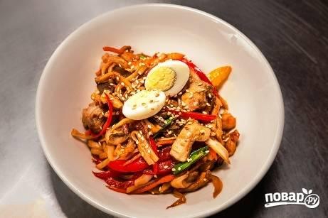 Готовую пшеничную лапшу с курицей и овощами выкладываем на тарелку. Украшаем свареным яйцом и посыпаем кунжутом.