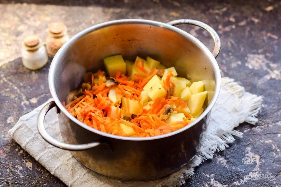 В кастрюлю переложите картофель. На сухой сковороде поджарьте немного морковь и грибы, добавьте к картофелю.