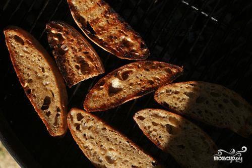 2. Разогреть сковороду, гриль или сковороду для панини  до средней температуры. Нарезать хлеб ломтиками и с  помощью кисти смазать с обеих сторон большим количеством оливкового масла. Приправить с обеих сторон солью и перцем. Обжарить хлеб, переворачивая один раз, пока он не подрумянится с обеих сторон.