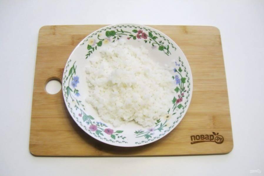 Рис отварите. Для этого крупу хорошо промойте и выложите в кастрюлю. Залейте водой в соотношении воды к рису 2:1. Посолите по вкусу. Варите до готовности риса. После воду слейте, а рис промойте чистой водой.