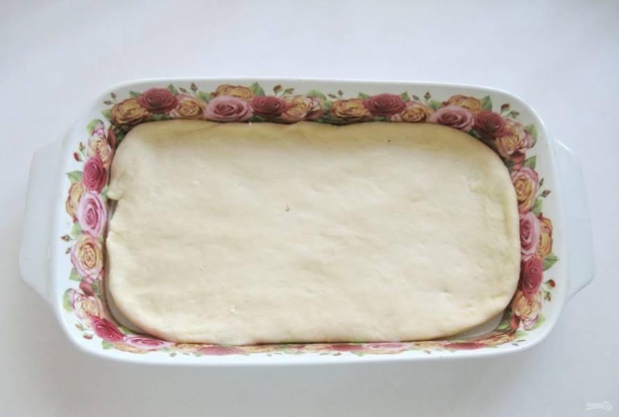 Достаньте тесто из миски, обомните и разделите на две неравные части. Большую часть раскатайте в пласт и выложите в форму для запекания.