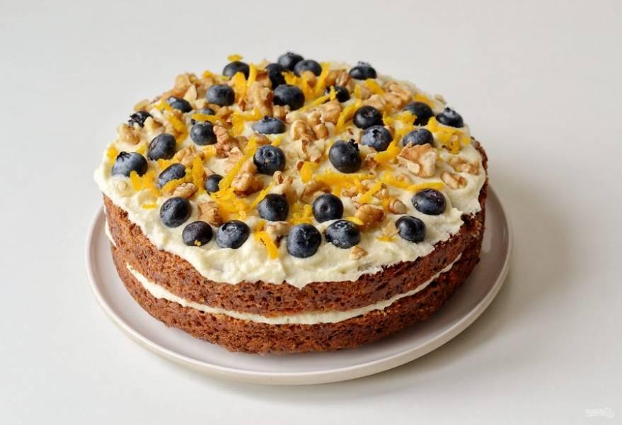 Накройте второй половиной бисквита, смажьте ее оставшимся кремом. Сверху украсьте ягодами, апельсиновой цедрой и грецкими орехами.