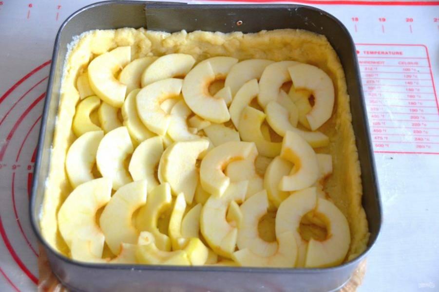 Из большей части теста в любой форме для выпечки (силиконовой, металлической)  сделайте основу для пирога с небольшими бортиками (примерно 2 см.), выложите ломтики яблок.