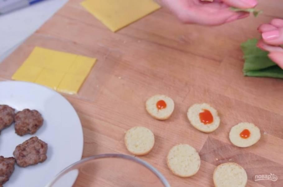 5. Фарш обжарьте на растительном масле с обеих сторон. Булочки разрежьте на две части, смажьте их соусом, добавьте листья салата, котлетки, помидоры и сыр.