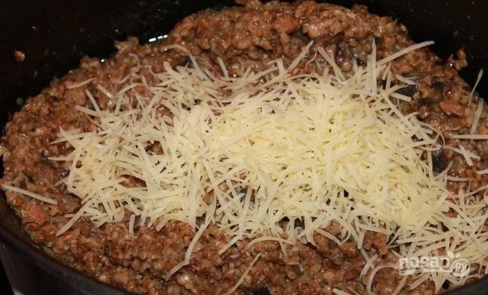 Твердый сыр натрите на крупной терке, 50 грамм сразу добавьте в сковороду, перемешайте, посолите по вкусу.