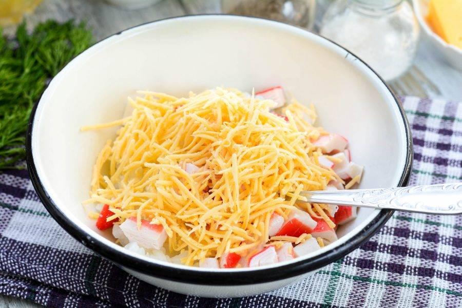 Натрите сыр на терке и всыпьте в салат.