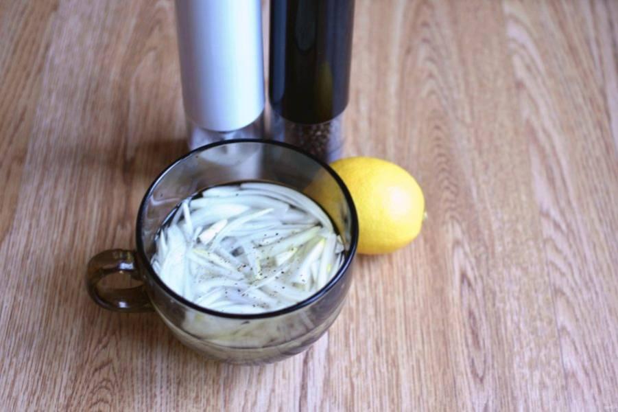 Лук тонко нашинкуйте и замаринуйте в смеси холодной воды с лимонным соком, солью и сахаром. Оставьте на 20 минут.
