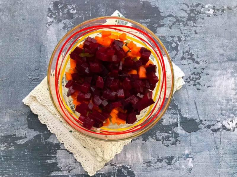 Вареную свеклу нарежьте кубиками и выложите в тарелку к остальным ингредиентам.