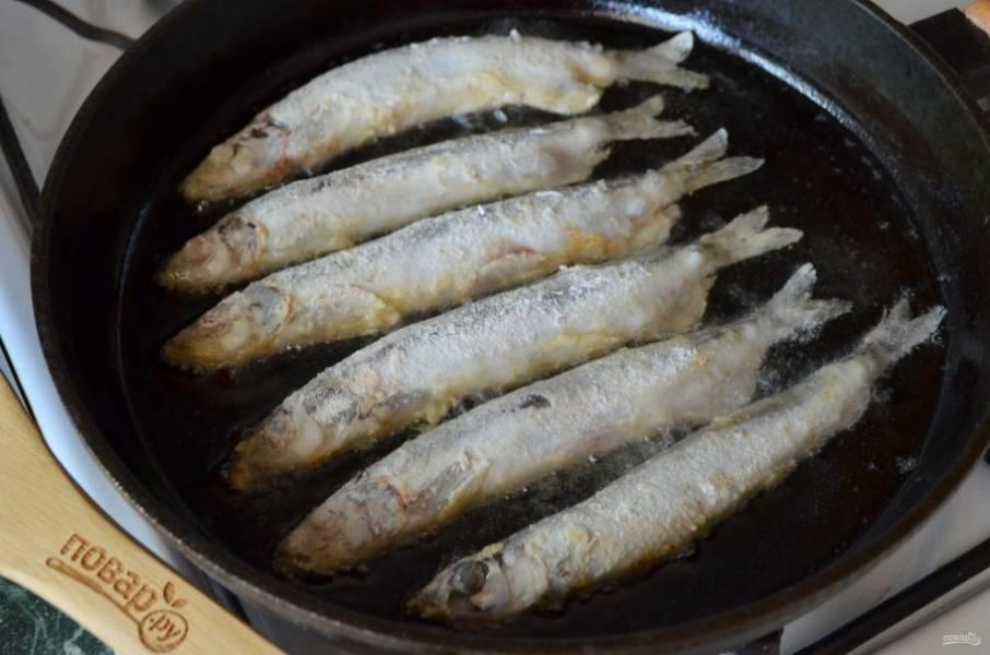 Поставьте сковороду на плиту, разогрейте масло. Выкладывайте мойву и жарьте на медленном огне до золотистой корочки. Не спешите переворачивать рыбу, пусть она хорошо поджарится сначала с одной стороны, потом с другой.