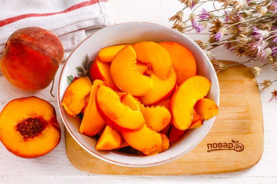 Персики промойте в воде, удаляя весь ворсистый слой с поверхности фруктов. Разделите на две части и удалите косточку. Нарежьте ломтиками или кубиками.