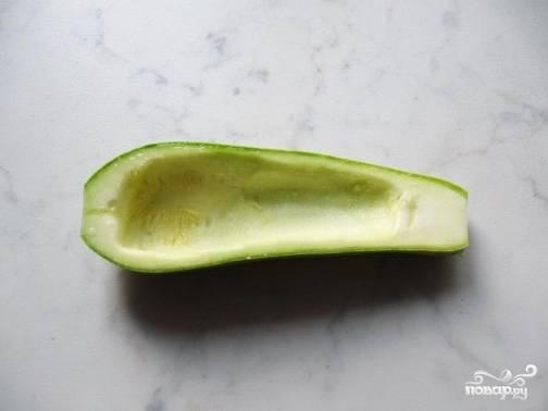 Молодые кабачки нужно хорошо помыть и разрезать вдоль, с помощью большой ложки удалите часть мякоти и семена.