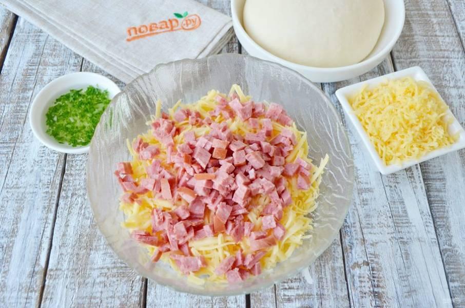 Натрите сыр на крупной терке, небольшую часть натрите на мелкой терке, это для посыпки сверху. Копченую колбасу порежьте мелкими кубиками. Смешайте сыр и колбасу.