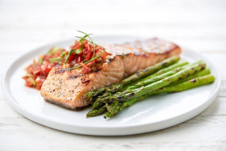 5. Подавайте рыбу со спаржей, салатом и зелёным луком. Приятного аппетита!