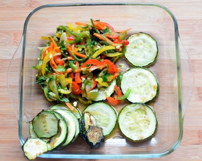 Выложите в удобную посуду слой кружочков цукини. Сверху - слой овощей с зеленью.