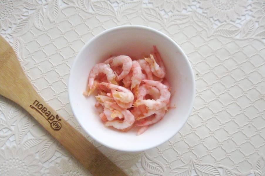 Варено-мороженые креветки промойте в горячей водой и очистите от панциря.