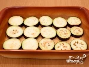 Теперь достаньте форму для запекания. На её дно уложите баклажаны, сверху посыпьте их чесноком. Далее — помидоры, которые следует посолить и поперчить. И в конце посыпьте всё сулугуни.