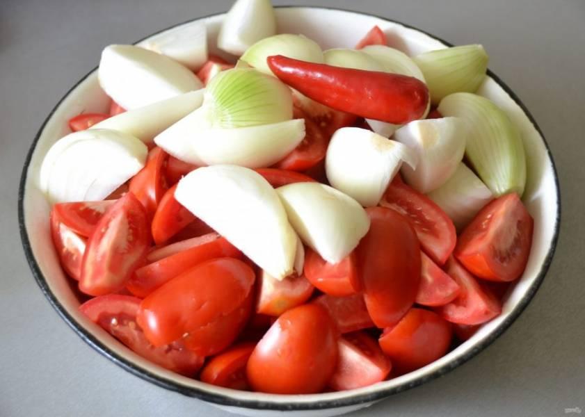 Хорошо промойте помидоры, удалите плодоножки, нарежьте на части, лук очистите и тоже порежьте на части, добавьте 1 острый перчик, всё это перекрутите через мясорубку.
