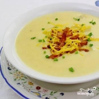 7. Выберите из супа веточки тимьяна. Снимите картофельный суп с огня и взбейте блендером. Добавьте сливки и тертый сыр. Прогрейте, помешивая, до растворения сыра. До кипения не доводите. Украсьте готовый картофельный суп-пюре беконом и измельченным зеленым луком. Приятного аппетита!