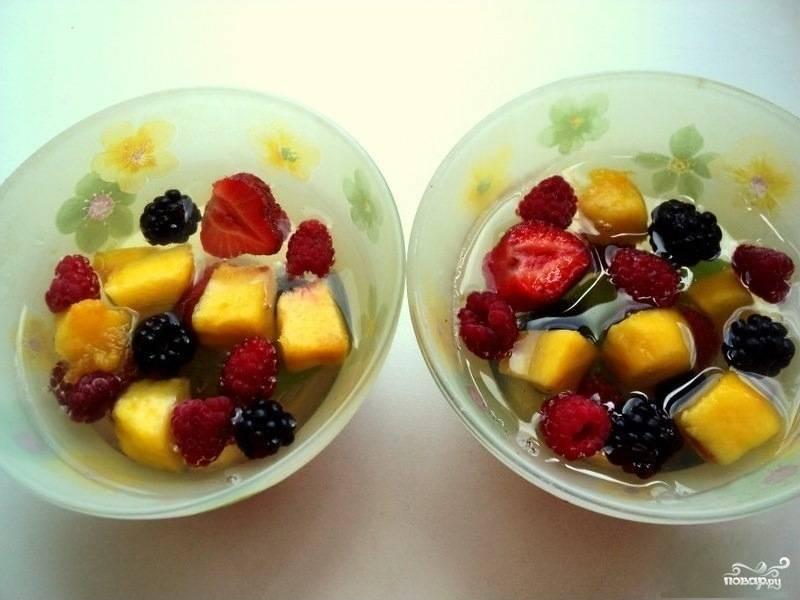 2.Персик очистите от кожицы, выньте косточку, а мякоть нарежьте кубиками. Ягоды промойте и просушите. В пиалки налейте немного желе, прокрутите их, чтобы оно растеклось по поверхности, и отправьте в морозилку приблизительно на 10 минут для застывания. Затем выложите в пиалки 1/3 часть персика, ягод и листьев мяты. Налейте часть желе, и опять поставьте в морозилку.