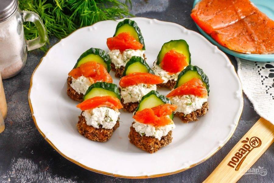 Нарежьте красную рыбу небольшими кусочками и выложите на творожный сыр. По желанию можно ломтики рыбы свернуть розочками или проколоть шпажками, чтобы она лучше держалась на канапе.