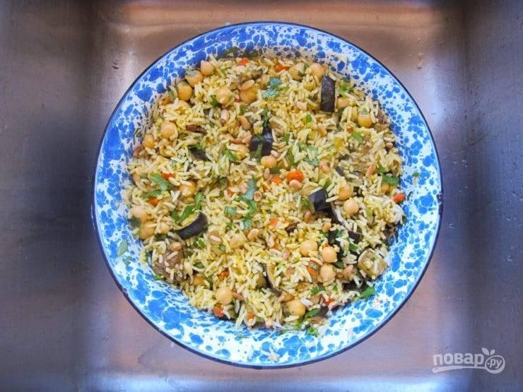 5. Далее вновь слейте воду с риса. Потом добавьте в него овощи, все приправы, соль и нут. Тщательно перемешайте массу в течение 2-х минут.