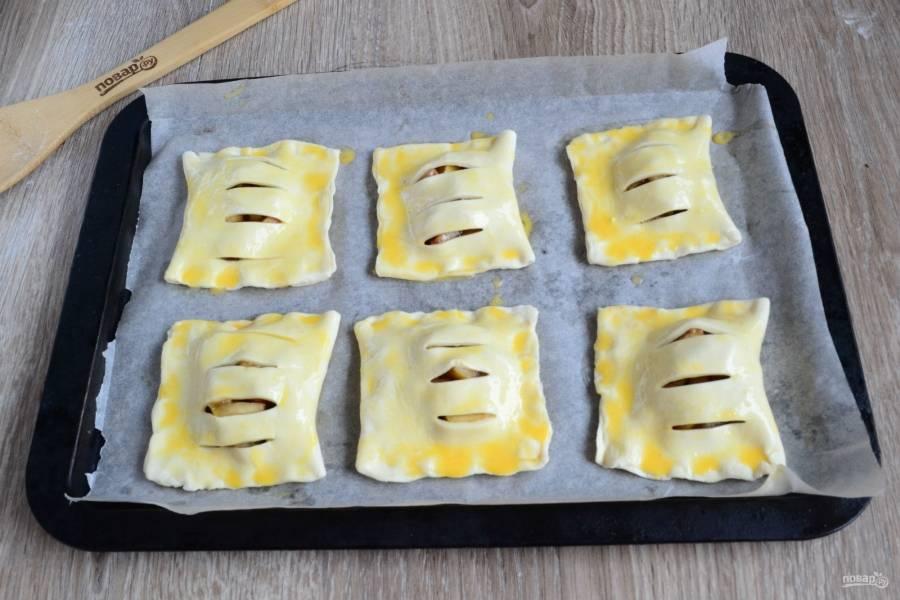 Переложите подготовленные слойки на противень, застеленный пергаментом, смажьте взбитым яйцом или смесью желтка с молоком. Отправьте слойки в заранее разогретую до 200 градусов духовку на 15-20 минут. Выпекайте до золотистого цвета.
