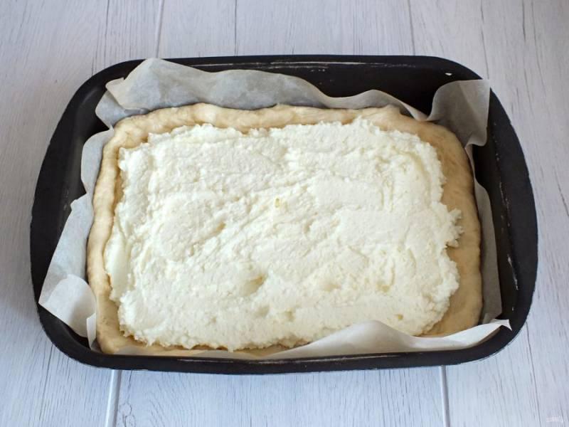 Возьмите противень или форму для выпечки. Застелите бумагой или смажьте маслом. Переложите в форму большой пласт теста. На него выложите начинку из творога, оставляя небольшое расстояние с краёв.